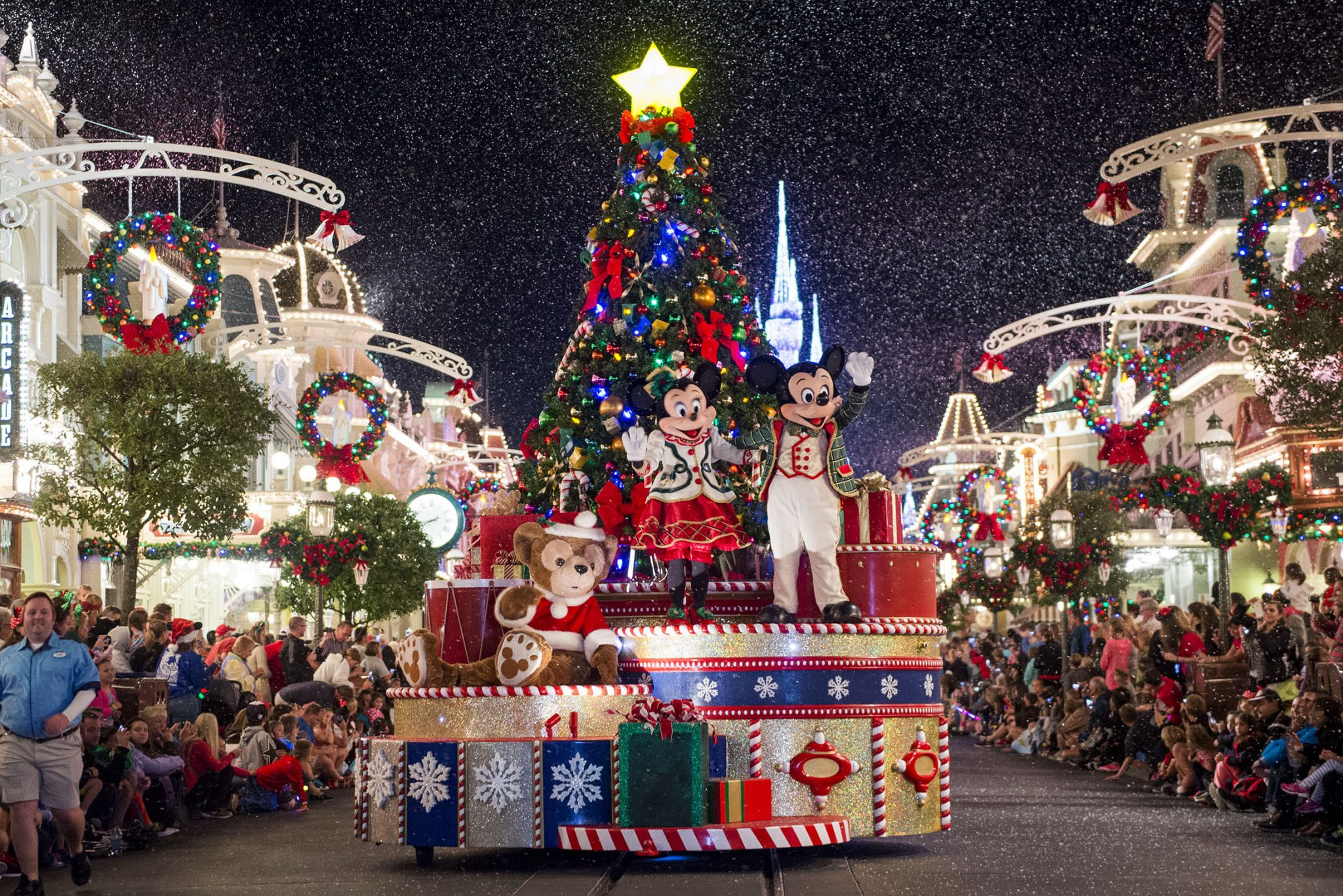"Mickey Mouse, Minnie Mouse and Duffy wave to Magic Kingdom guests as snow falls on Main Street, U.S.A., during "" Mickey's Once Upon a Christmastime Parade"" at Walt Disney World Resort. The festive processional is one of the happy highlights of Mickey's Very Merry Christmas Party, a night of holiday splendor with lively stage shows, a unique holiday parade, Holiday Wishes: Celebrate the Spirit of the Season nighttime fireworks, and snow flurries on Main Street, U.S.A. The special-ticket event takes place on select nights in November and December at Magic Kingdom in Lake Buena Vista, Fla. (Ryan Wendler, photographer)"